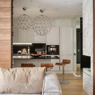 Идея дизайна: кухня в современном стиле с белыми фасадами, черным фартуком, светлым паркетным полом, островом, бежевым полом и черной столешницей