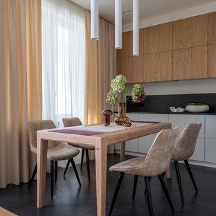 Свежая идея для дизайна: кухня в современном стиле с черным полом, плоскими фасадами, фасадами цвета дерева среднего тона, черным фартуком и черной столешницей - отличное фото интерьера