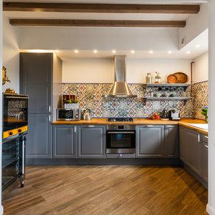 Идея дизайна: угловая кухня в стиле кантри с обеденным столом, накладной раковиной, фасадами с выступающей филенкой, серыми фасадами, столешницей из дерева, разноцветным фартуком, техникой из нержавеющей стали и коричневым полом без острова