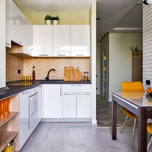 Свежая идея для дизайна: угловая кухня в современном стиле с накладной раковиной, плоскими фасадами, белыми фасадами, оранжевым фартуком, фартуком из плитки мозаики, белой техникой, серым полом, черной столешницей и обеденным столом без острова - отличное фото интерьера