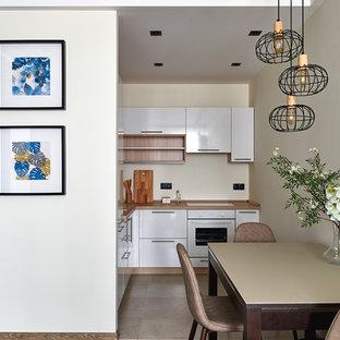 Свежая идея для дизайна: угловая кухня-гостиная в стиле современная классика с плоскими фасадами, белыми фасадами, бежевым фартуком, белой техникой, бежевым полом, коричневой столешницей и деревянной столешницей без острова - отличное фото интерьера