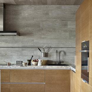 Пример оригинального дизайна интерьера: угловая кухня в современном стиле с накладной раковиной, плоскими фасадами, фасадами цвета дерева среднего тона, серым фартуком, черной техникой, серым полом, серой столешницей и полом из керамической плитки