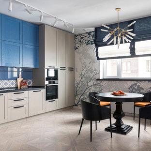 На фото: угловая кухня в стиле современная классика с обеденным столом, фасадами в стиле шейкер, синими фасадами, разноцветным фартуком, техникой из нержавеющей стали, бежевым полом и черной столешницей без острова