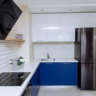 他の地域の中くらいのトランジショナルスタイルのおしゃれなキッチン (アンダーカウンターシンク、落し込みパネル扉のキャビネット、青いキャビネット、人工大理石カウンター、白いキッチンパネル、レンガのキッチンパネル、黒い調理設備、セラミックタイルの床、白い床、白いキッチンカウンター) の写真