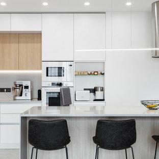 Стильный дизайн: угловая кухня-гостиная среднего размера в современном стиле с врезной раковиной, плоскими фасадами, белыми фасадами, столешницей из акрилового камня, серым фартуком, белой техникой, полом из керамогранита, полуостровом, серым полом, серой столешницей и многоуровневым потолком - последний тренд