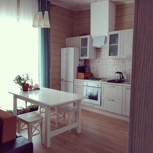 This is an example of a small contemporary single-wall eat-in kitchen in Moscow with glass-front cabinets, beige cabinets, laminate benchtops, multi-coloured splashback, ceramic splashback, white appliances, laminate floors, brown floor, beige benchtop and no island.