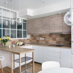 サンクトペテルブルクの中くらいの北欧スタイルのおしゃれなキッチン (フラットパネル扉のキャビネット、淡色木目調キャビネット、木材カウンター、木材のキッチンパネル、白い調理設備、ラミネートの床、アイランドなし、ベージュの床、ドロップインシンク、茶色いキッチンパネル) の写真