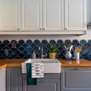 Стильный дизайн: угловая кухня в морском стиле с раковиной в стиле кантри, фасадами с выступающей филенкой, серыми фасадами, столешницей из дерева, синим фартуком и фартуком из керамической плитки - последний тренд