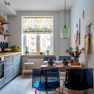 Неиссякаемый источник вдохновения для домашнего уюта: отдельная кухня в современном стиле с фасадами с выступающей филенкой, серыми фасадами, столешницей из дерева, синим фартуком, фартуком из керамической плитки, техникой из нержавеющей стали и коричневой столешницей без острова