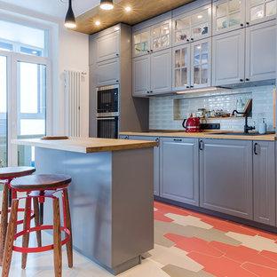 Стильный дизайн: линейная кухня-гостиная в современном стиле с накладной раковиной, фасадами с выступающей филенкой, серыми фасадами, деревянной столешницей, белым фартуком, техникой из нержавеющей стали, островом и разноцветным полом - последний тренд
