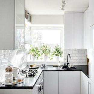 Ejemplo de cocina en U, escandinava, pequeña, sin isla, con fregadero encastrado, armarios con paneles lisos, puertas de armario blancas y salpicadero de vidrio