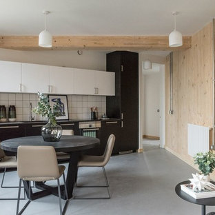 Scandinavian single-wall kitchen/diner in London with a single-bowl sink, flat-panel cabinets, black cabinets, white splashback, black appliances, concrete flooring, no island and grey floors.