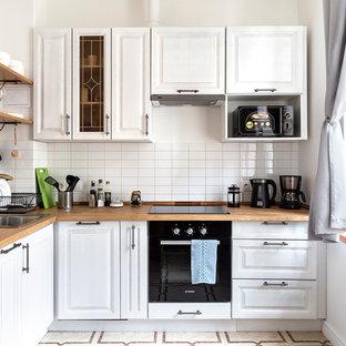 На фото: угловая кухня среднего размера в скандинавском стиле с обеденным столом, накладной раковиной, фасадами с выступающей филенкой, белыми фасадами, деревянной столешницей, белым фартуком, фартуком из плитки кабанчик, черной техникой, полом из керамической плитки, бежевым полом и коричневой столешницей без острова