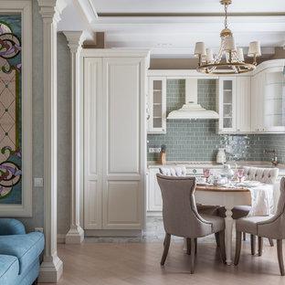 На фото: угловая кухня-гостиная в стиле современная классика с белыми фасадами, зеленым фартуком и белой техникой без острова с