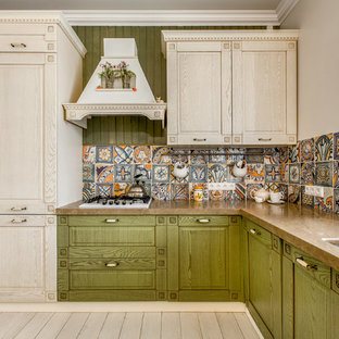 Country l-shaped kitchen in Other with an undermount sink, green cabinets, multi-coloured splashback, raised-panel cabinets and white appliances.