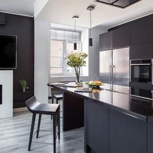 Стильный дизайн: линейная кухня-гостиная среднего размера в современном стиле с плоскими фасадами, черными фасадами, столешницей из акрилового камня, черным фартуком, техникой из нержавеющей стали, пробковым полом, островом, серым полом и черной столешницей - последний тренд
