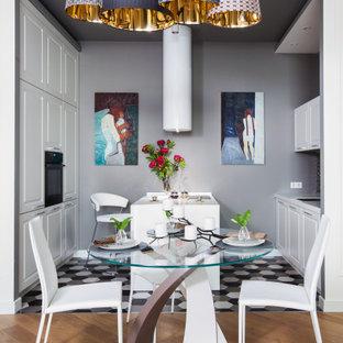 На фото: параллельная кухня в современном стиле с обеденным столом, фасадами с выступающей филенкой, белыми фасадами, черной техникой, полуостровом, разноцветным полом и белой столешницей с