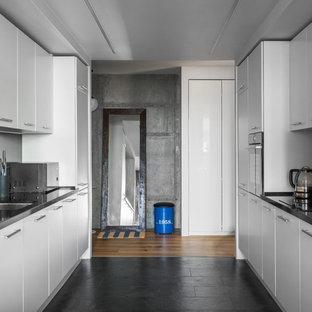 Пример оригинального дизайна интерьера: параллельная кухня в стиле лофт с врезной раковиной, плоскими фасадами, белыми фасадами, черным полом и черной столешницей без острова