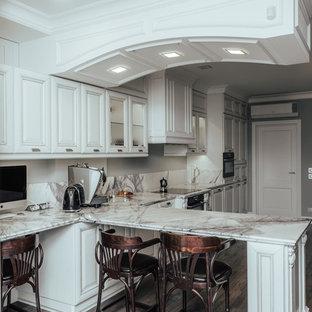 На фото: кухни в стиле современная классика с фасадами с выступающей филенкой, белыми фасадами, серым фартуком, черной техникой, полуостровом и коричневым полом
