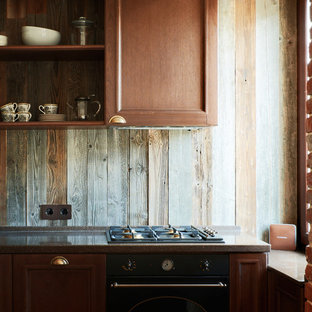 Inspiration for a small industrial l-shaped eat-in kitchen in Moscow with an undermount sink, raised-panel cabinets, medium wood cabinets, solid surface benchtops, brown splashback, black appliances, porcelain floors and with island.