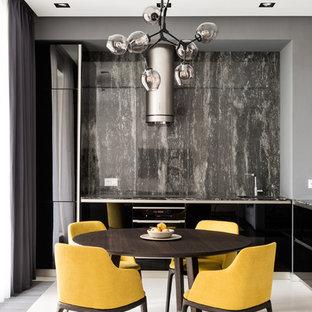 Удачное сочетание для дизайна помещения: угловая кухня-гостиная в современном стиле с плоскими фасадами, черными фасадами, серым фартуком, черной техникой, белым полом и черной столешницей без острова - самое интересное для вас