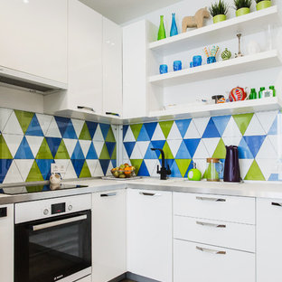 Photo of a small contemporary l-shaped kitchen in Moscow with flat-panel cabinets, white cabinets, solid surface benchtops, multi-coloured splashback, ceramic splashback, white appliances, light hardwood floors, no island and a drop-in sink.