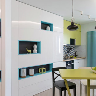 Inspiration for a small contemporary single-wall open plan kitchen in Other with a single-bowl sink, flat-panel cabinets, green cabinets, wood benchtops, multi-coloured splashback, ceramic splashback, stainless steel appliances, laminate floors, with island, beige floor and green benchtop.