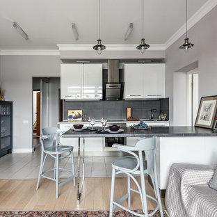 На фото: линейная кухня-гостиная в скандинавском стиле с плоскими фасадами, белыми фасадами, серым фартуком, техникой из нержавеющей стали, островом и серой столешницей с