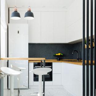 Пример оригинального дизайна: маленькая угловая кухня-гостиная в современном стиле с плоскими фасадами, белыми фасадами, деревянной столешницей, черным фартуком, фартуком из керамогранитной плитки, белым полом, накладной раковиной, черной техникой и коричневой столешницей