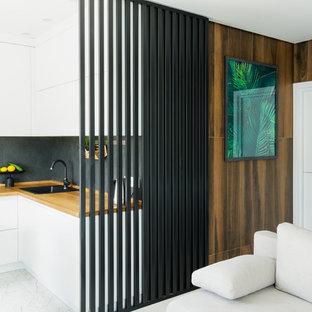 Стильный дизайн: маленькая угловая кухня-гостиная в современном стиле с плоскими фасадами, белыми фасадами, столешницей из дерева, черным фартуком, фартуком из керамогранитной плитки, белым полом, накладной раковиной, черной техникой и коричневой столешницей - последний тренд