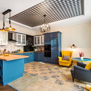 Пример оригинального дизайна интерьера: большая п-образная кухня в классическом стиле с обеденным столом, стеклянными фасадами, синими фасадами, столешницей из дерева, разноцветным фартуком, черной техникой и полуостровом