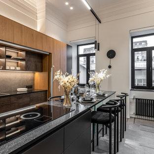 他の地域の広いコンテンポラリースタイルのおしゃれなキッチン (ドロップインシンク、フラットパネル扉のキャビネット、中間色木目調キャビネット、グレーのキッチンパネル、パネルと同色の調理設備、グレーの床、黒いキッチンカウンター) の写真