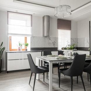 Пример оригинального дизайна: угловая кухня в современном стиле с обеденным столом, плоскими фасадами, белыми фасадами, техникой из нержавеющей стали, паркетным полом среднего тона, серым полом, черной столешницей и многоуровневым потолком