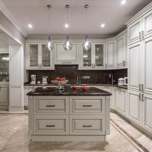 Пример оригинального дизайна интерьера: большая угловая кухня в классическом стиле с обеденным столом, врезной раковиной, белыми фасадами, мраморной столешницей, коричневым фартуком, белой техникой, мраморным полом, островом, фасадами с выступающей филенкой и фартуком из плитки мозаики
