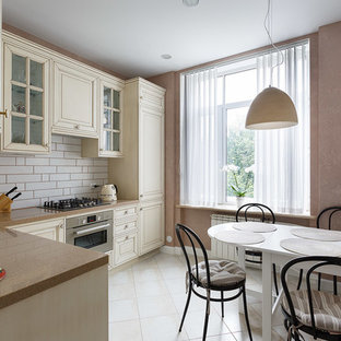 Design ideas for a small traditional l-shaped separate kitchen in Saint Petersburg with a drop-in sink, raised-panel cabinets, beige cabinets, solid surface benchtops, white splashback, ceramic splashback, coloured appliances, porcelain floors, no island, beige floor and brown benchtop.