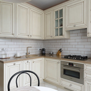 Small traditional l-shaped separate kitchen in Saint Petersburg with a drop-in sink, recessed-panel cabinets, beige cabinets, solid surface benchtops, white splashback, ceramic splashback, coloured appliances, porcelain floors, no island, beige floor and brown benchtop.