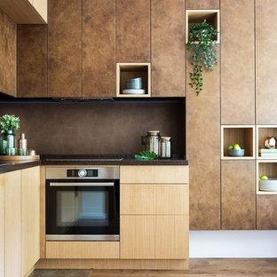 На фото: угловая кухня в современном стиле с плоскими фасадами, коричневыми фасадами, коричневым фартуком и коричневым полом с