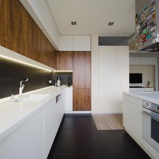 Идея дизайна: большая угловая кухня-гостиная в современном стиле с врезной раковиной, плоскими фасадами, белыми фасадами, столешницей из акрилового камня, черным фартуком, фартуком из керамогранитной плитки, белой техникой, полом из керамической плитки, островом и черным полом