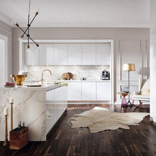 На фото: кухня среднего размера в современном стиле с обеденным столом, белыми фасадами, белым фартуком, островом, плоскими фасадами, темным паркетным полом, коричневым полом и техникой из нержавеющей стали с