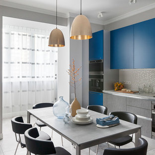 На фото: большая кухня в современном стиле с обеденным столом, плоскими фасадами, синими фасадами, фартуком цвета металлик, черной техникой, серым полом и серой столешницей