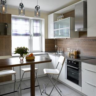 На фото: отдельная, угловая кухня в современном стиле с плоскими фасадами, белыми фасадами, коричневым фартуком, техникой из нержавеющей стали и серым полом с
