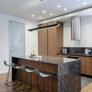 Свежая идея для дизайна: прямая кухня в современном стиле с плоскими фасадами, фасадами цвета дерева среднего тона, серым фартуком, светлым паркетным полом, островом, бежевым полом и серой столешницей - отличное фото интерьера
