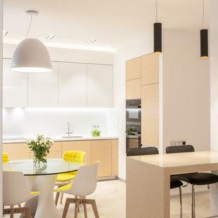 Стильный дизайн: кухня-гостиная в современном стиле с врезной раковиной, плоскими фасадами, белыми фасадами, белым фартуком, черной техникой, бежевым полом и белой столешницей - последний тренд