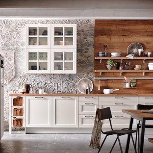 На фото: доступные линейные кухни - столовые среднего размера в классическом стиле с белыми фасадами, фасадами с утопленной филенкой, столешницей из дерева, бетонным полом и серым полом без острова