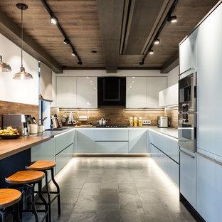Идея дизайна: большая п-образная кухня в современном стиле с плоскими фасадами, коричневым фартуком, фартуком из дерева, полом из керамогранита, серым полом, накладной раковиной и белыми фасадами без острова