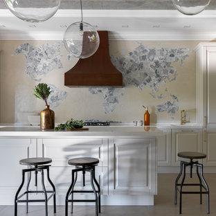 На фото: прямая кухня в современном стиле с обеденным столом, белыми фасадами, полом из керамогранита, серым полом, бежевым фартуком, островом, белой столешницей, фасадами с выступающей филенкой и техникой под мебельный фасад с