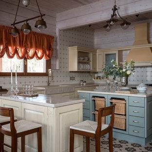 Пример оригинального дизайна: п-образная кухня в стиле кантри с раковиной в стиле кантри, фасадами с выступающей филенкой, бежевыми фасадами, бежевым фартуком, островом, разноцветным полом и бежевой столешницей