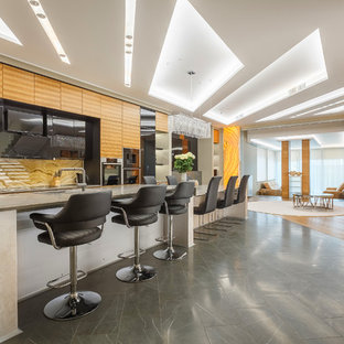 Свежая идея для дизайна: линейная кухня-гостиная в современном стиле с накладной раковиной, плоскими фасадами, черными фасадами, бежевым фартуком, островом, серым полом и черной техникой - отличное фото интерьера