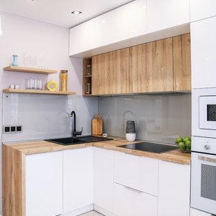 Стильный дизайн: маленькая угловая кухня в современном стиле с накладной раковиной, плоскими фасадами, белыми фасадами, деревянной столешницей, серым фартуком, фартуком из стекла, белой техникой и бежевым полом - последний тренд