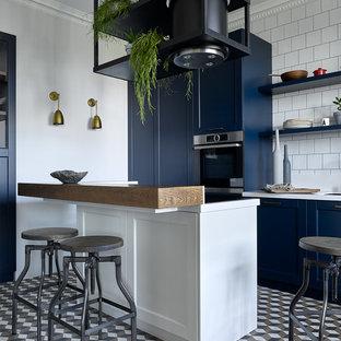 Пример оригинального дизайна: прямая кухня в современном стиле с врезной раковиной, фасадами в стиле шейкер, синими фасадами, белым фартуком, техникой из нержавеющей стали, островом, разноцветным полом и белой столешницей